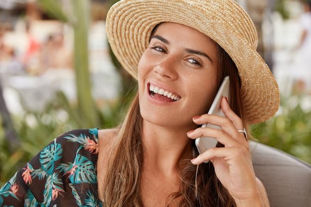 Ziemlich fröhliche frau mit strohhut, die sich während der sommerferien im tropischen urlaubsland neu erschafft, über ein smartphone mit verwandten spricht, kostenloses roaming nutzt und ein breites, strahlendes lächeln hat. lifestyle-konzept