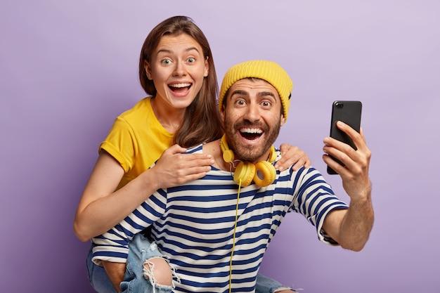 Ziemlich fröhliche frau reitet auf dem rücken ihres freundes, macht selfie, hat fröhliche ausdrücke