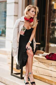Ziemlich gelangweiltes mädchen in schwarzen sandalen, die jemanden warten und champagner nahe restaurant trinken