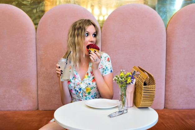 Ziemlich glückliche blonde hipster-frau, die leckeren himbeer-dessertkuchen isst, bei niedlicher bäckerei sitzt, ihr essen, süßes frühstück, diät-ernährungskonzept genießt.
