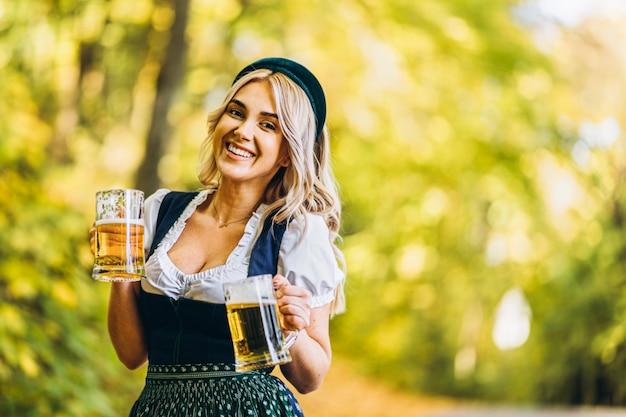 Ziemlich glückliche blondine im dirndl, traditionelles festkleid, zwei krug bier draußen im wald haltend