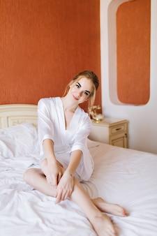 Ziemlich glückliche braut im weißen batrobe, der am morgen auf bett sitzt. sie lächelte in die kamera