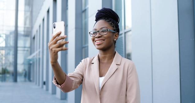 Ziemlich glückliche junge afroamerikanische junge frau in den gläsern, die videochat auf smartphone im freien am geschäftsgebäude haben. freudige schöne frau, die über webcam auf handy spricht und videochatting.