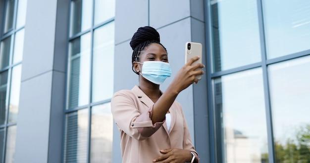 Ziemlich glückliche junge afroamerikanische junge frau in der medizinischen maske, die videochat auf smartphone im freien am geschäftsgebäude hat. fröhliche schöne frau, die über webcam auf handy spricht und videochatting.