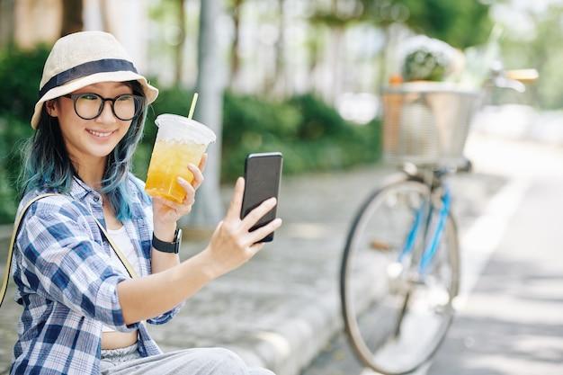 Ziemlich glückliche junge chinesische frau in gläsern und eimerhut, die selfie mit erfrischendem getränk nehmen