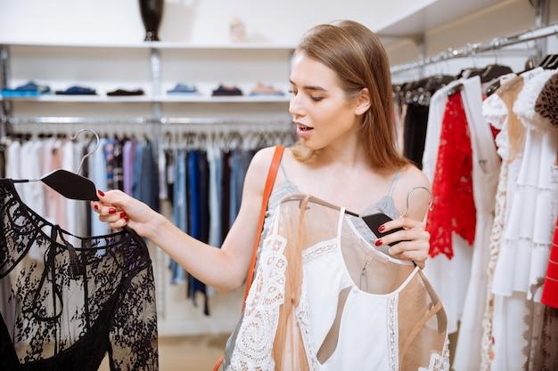 Ziemlich glückliche junge frau, die zwischen zwei kleidern im bekleidungsgeschäft wählt