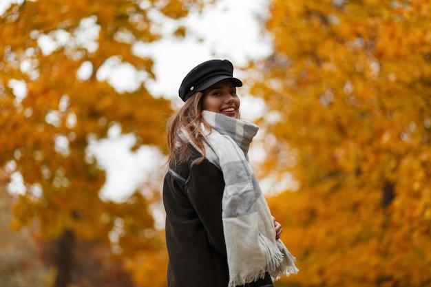 Ziemlich glückliche junge frau in einem schönen lächeln in einem trendigen hut in einer jacke mit einem vintage-schal posiert in einem park auf einem hintergrund von orange-gelbem laub. lustiges attraktives stilvolles mädchenmodell im freien.