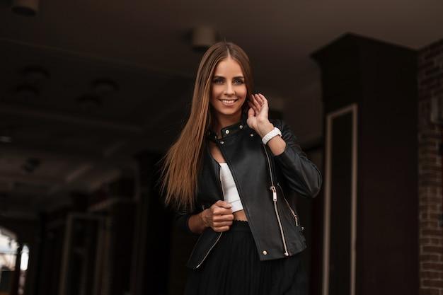 Ziemlich glückliche junge frau mit niedlichem lächeln in einer stilvollen schwarzen lederjacke in einer eleganten bluse, die in der stadt in einer dunklen straße aufwirft. schönes fröhliches mädchenmodemodell genießt einen spaziergang. jugendstil.