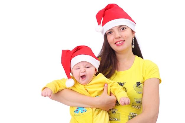 Ziemlich glückliche junge mutter mit dem süßen kleinen baby in neujahrsmützen