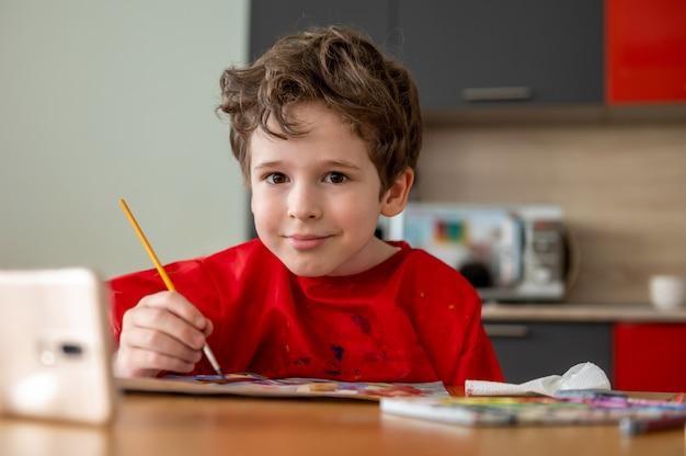 Ziemlich glücklicher kleiner junge, der zu hause mit online-fernunterricht zeichnet