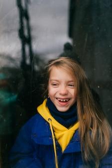 Ziemlich glückliches junges kaukasisches mädchen mit langen blonden haaren