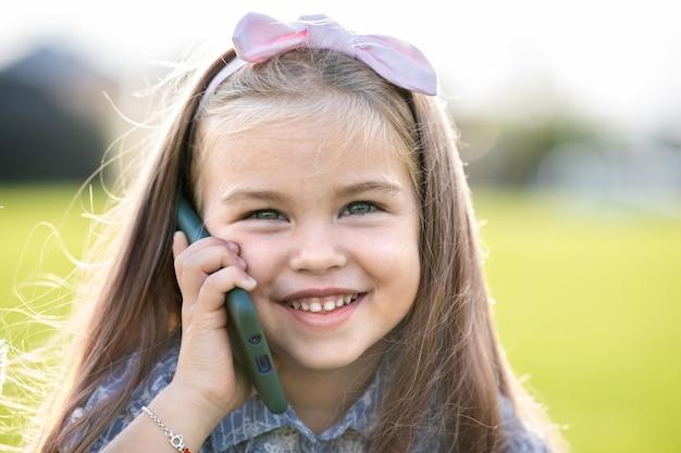 Ziemlich glückliches kindermädchen, das auf handy spricht, das im sommer draußen lächelt.
