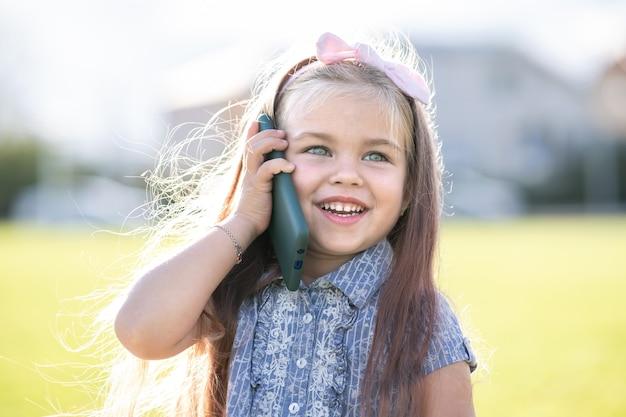 Ziemlich glückliches kindermädchen, das im sommer am handy lächelt und im freien spricht.