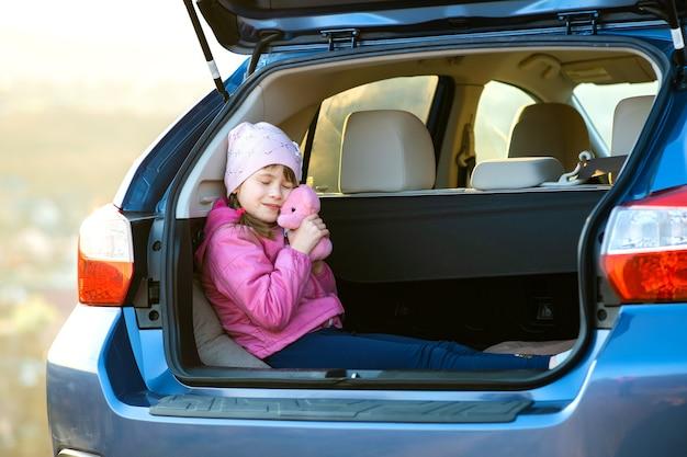 Ziemlich glückliches kindermädchen, das mit einem rosa spielzeug-teddybär in einem kofferraum spielt.