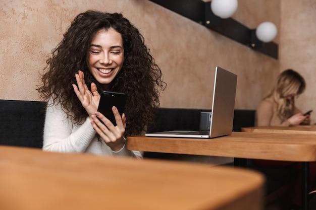 Ziemlich glückliches mädchen sitzt im café mit laptop-computer und handy winken