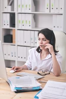 Ziemlich junger seriöser bediener mit headset, der mit kunden spricht und ihre fragen online beantwortet, während er vor dem computer arbeitet
