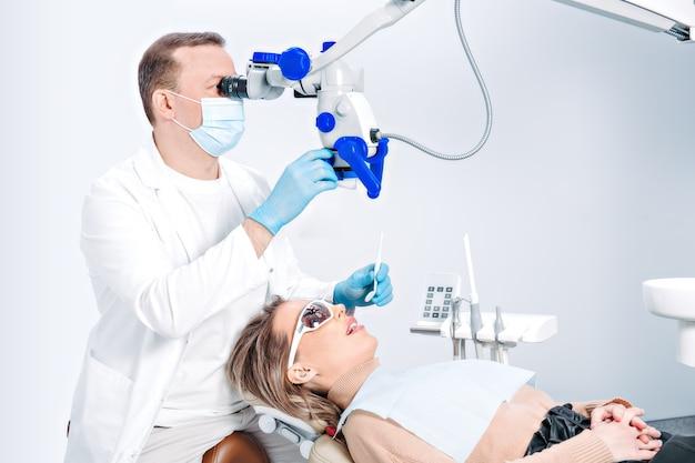 Ziemlich kaukasische frau im zahnarztstuhl in der modernen zahnklinik. arzt untersucht den patienten mit zahnärztlicher ausrüstung, mikroskop. patientin, die zahnpflege erhält.