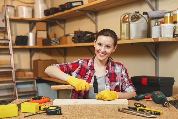 Ziemlich kaukasische junge braunhaarige frau in kariertem hemd, grauem t-shirt, gelben handschuhen, die in der tischlerei am holztisch mit verschiedenen werkzeugen arbeiten, nägel mit hammer ins brett hämmern.