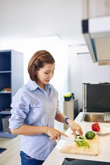 Ziemlich lächelnde asiatische hausfrau, die frisches gemüse für köstliches gesundes gericht schneidet