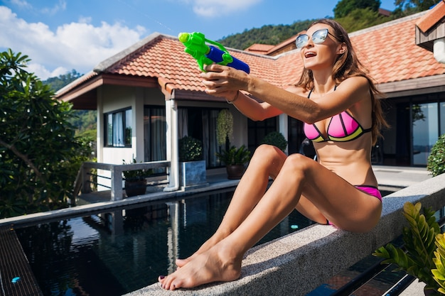 Ziemlich lächelnde glückliche frau, die mit wassergewehrspielzeug am pool im tropischen sommerurlaub auf villenhotel spielt, das spaß im bikini-badeanzug, im bunten stil, in der partystimmung spielt