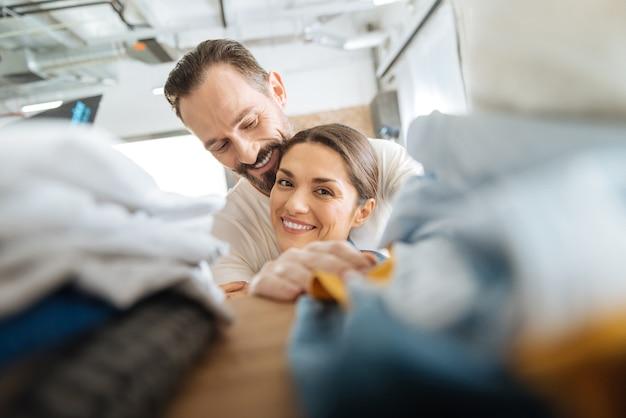 Ziemlich liebevolles junges paar, das wäsche macht, während es lacht und umarmt