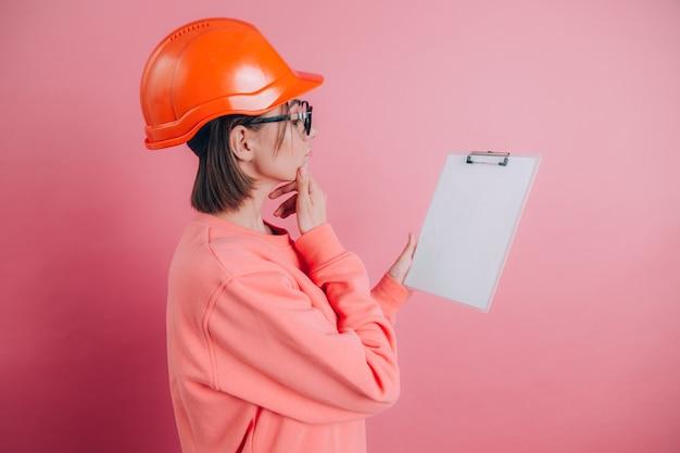 Ziemlich nachdenkliche arbeiterin des bauherrn halten weißes schild leer vor rosa hintergrund. bauhelm.