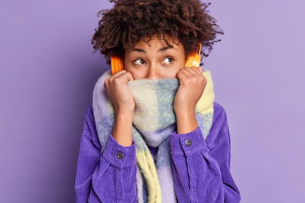 Ziemlich nachdenkliche frau fühlt sich sehr kalt nach dem gehen auf eisigem wetter trägt schal bedeckt die hälfte des gesichts zittert während des spaziergangs im freien trägt stereo-kopfhörer hört musik in lila hemd gekleidet