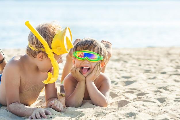 Ziemlich niedliche kinder am strand, die spaß haben. lächelnde kinder in der sommerzeit. jungs draußen.