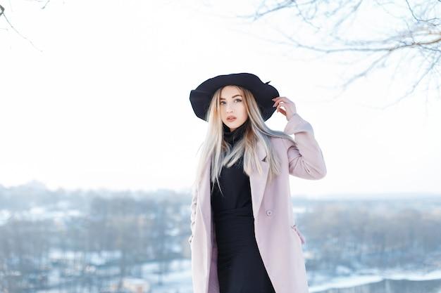 Ziemlich niedliche schöne junge frau mit blonden haaren in einem vintage rosa mantel in einem stilvollen hut in golf in einem rock steht auf der straße an einem sonnigen wintertag. modisches mädchen geht draußen.