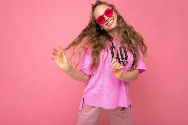 Ziemlich positiv lächelnde junge blonde lockige frau isoliert über rosa hintergrundwand mit lässigem rosa t-shirt und stilvoller bunter sonnenbrille mit blick in die kamera