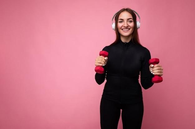 Ziemlich positiv lächelnde junge brünette frau, die schwarze sportkleidung trägt, die über rosa isoliert ist?