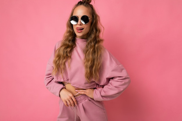 Ziemlich positive junge blonde lockige frau isoliert über rosa hintergrundwand mit lässiger rosa sportkleidung und stilvoller sonnenbrille mit blick auf die kamera.