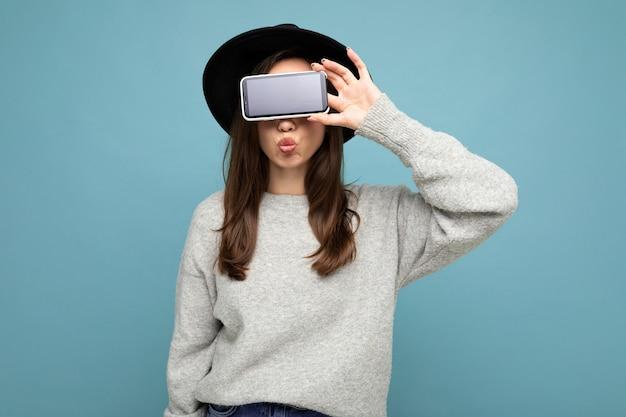 Ziemlich positive junge weibliche person, die schwarzen hut und grauen pullover hält telefon hält smartphone zeigt