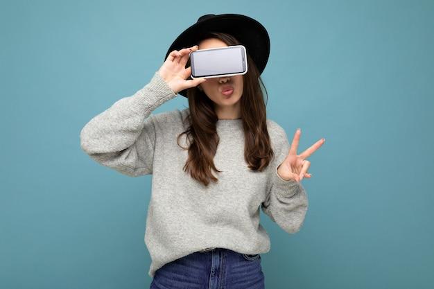 Ziemlich positive junge weibliche person mit schwarzem hut und grauem pullover mit telefon, das smartphone einzeln auf dem hintergrund zeigt, das friedensgeste zeigt und kuss gibt. attrappe, lehrmodell, simulation