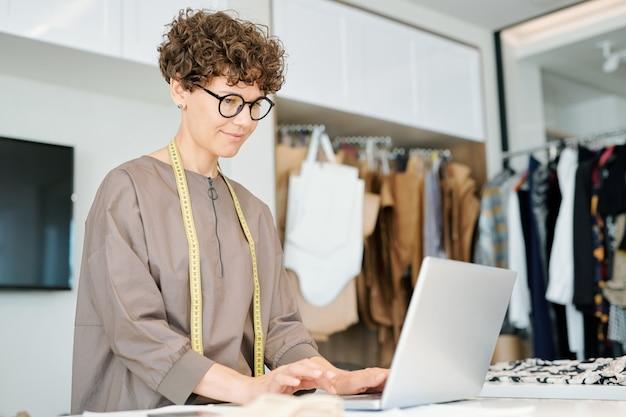 Ziemlich professionell im kleidungsdesign, das vor dem laptop steht, während er nach online-daten sucht oder über neues projekt arbeitet