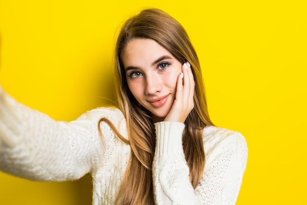 Ziemlich reizendes lächelndes sonniges modisches mädchen macht selfie auf ihrem telefon, das breiten weißen pullover auf gelb trägt