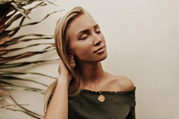 Ziemlich ruhige junge gebräunte blonde frau in dunkelgrüner spitze mit goldenen medaillon-posen mit geschlossenen augen nahe weißer wand mit palmblatt