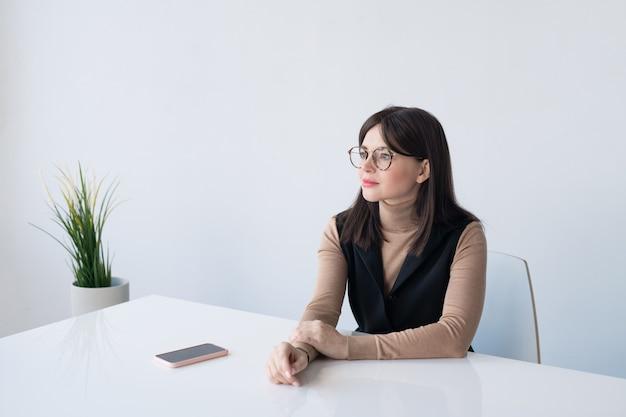 Ziemlich ruhige junge geschäftsfrau im intelligenten lässigen sitzen am schreibtisch gegen weiße wand im büro während der arbeit
