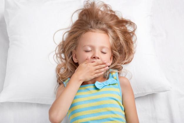 Ziemlich schläfrig schönes kleines weibliches mädchen hält die augen geschlossen, handfläche auf dem mund, gekleidet in lässig gestreifte nachtwäsche, liegt auf einem bequemen bett, wacht nach dem schlafen auf. kinder, guten morgen konzept