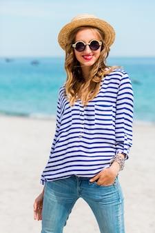 Ziemlich schlanke tan blonde blonde stilvolle frau in strohhut und sonnenbrille, posierend auf dem paradiesischen tropischen strand