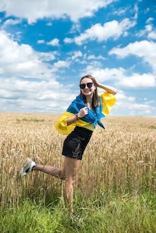 Ziemlich schlankes mädchen mit gelb-blauer flagge der ukraine im weizenfeld. lebensstil