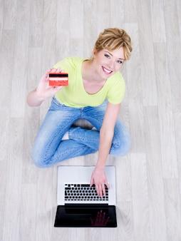 Ziemlich schöne junge frau, die auf dem boden mit kreditkarte sitzt und laptop verwendet