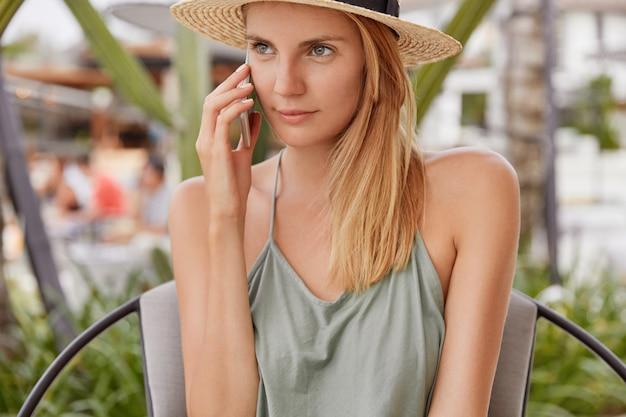 Ziemlich schöne junge frau, lässig gekleidet, hat ein mobiles gespräch mit einem freund, sitzt in der café-bar im freien, wartet auf bestellung, bespricht zukünftige pläne für den urlaub. blonde touristin rekonstruieren auf resort