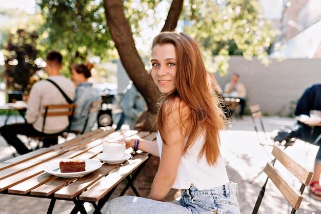 Ziemlich schöne junge frau mit langen hellbraunen haaren gekleidet weißes t-shirt