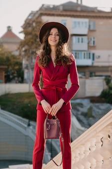 Ziemlich schöne stilvolle frau im lila anzug, der in der stadtstraße, modetrend der frühlingssommerherbstsaison trägt hut trägt und geldbörse hält