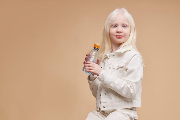 Ziemlich schönes kaukasisches albino-kind, das mit wasserflasche sitzt