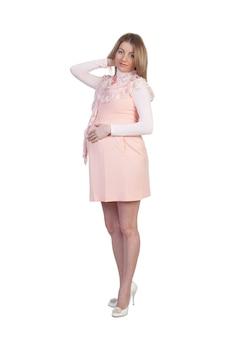 Ziemlich schwangere frau im rosa kleid isoliert auf weiß