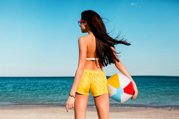 Ziemlich sexy sportliche bräunungsfrau, die ball am sommerstrand spielt. trage gelbe hemden, buntes oberteil und coole brille.