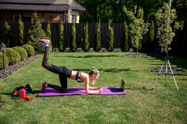 Ziemlich sportliche fitness-trainerin, die laptop während des online-videotrainings verwendet