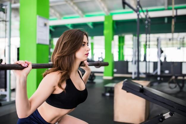 Ziemlich starke junge frau, die übungen macht, die mit langhantel hocken, gekleidet in modesportbekleidung im sportclub